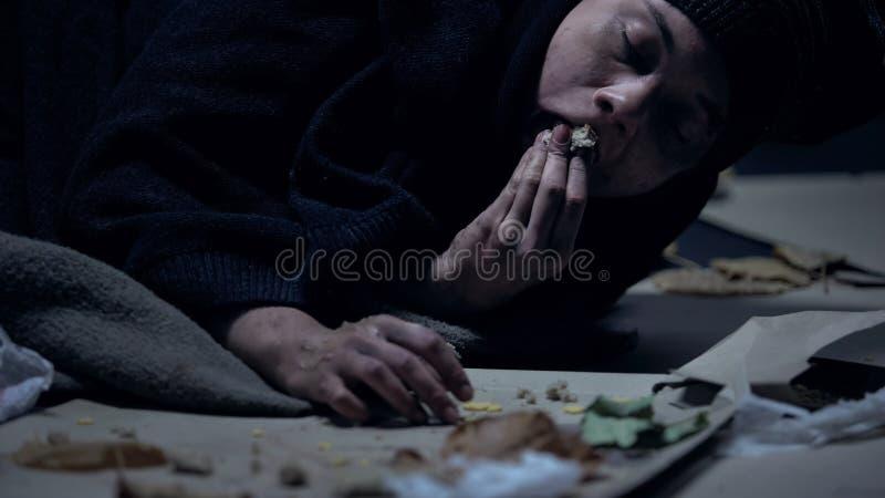 Hongerige dakloze op grond met huisvuil ligt en greedily persoon die orts eet royalty-vrije stock foto