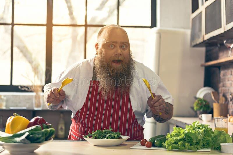 Hongerige dikke kerel die gehakte groenten mengen stock foto