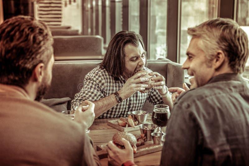 Hongerige longhaired mens die hamburger met genoegen eten stock fotografie