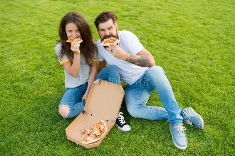 Hongerige mensen Eenvoudig geluk Bedrieg maaltijd Paar die pizza het ontspannen op groen gazon eten snel voedsellevering Gebaarde stock afbeelding