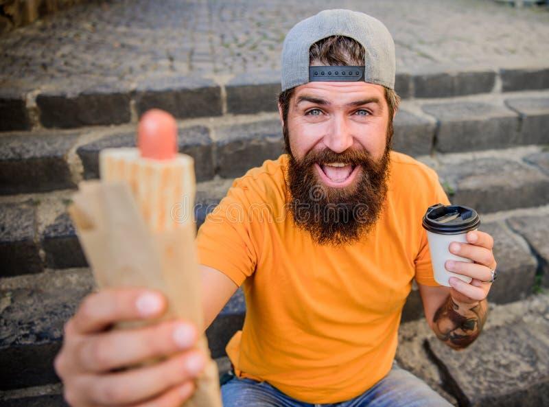 Hongerige mensensnack Kerel die hotdog eten Smakelijke worst van de mensen de gebaarde beet en drankdocument kop Zo goed straatvo stock afbeelding