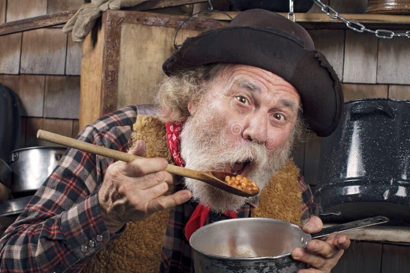 Hongerige oude cowboy die bonen van een steelpan eet stock afbeelding