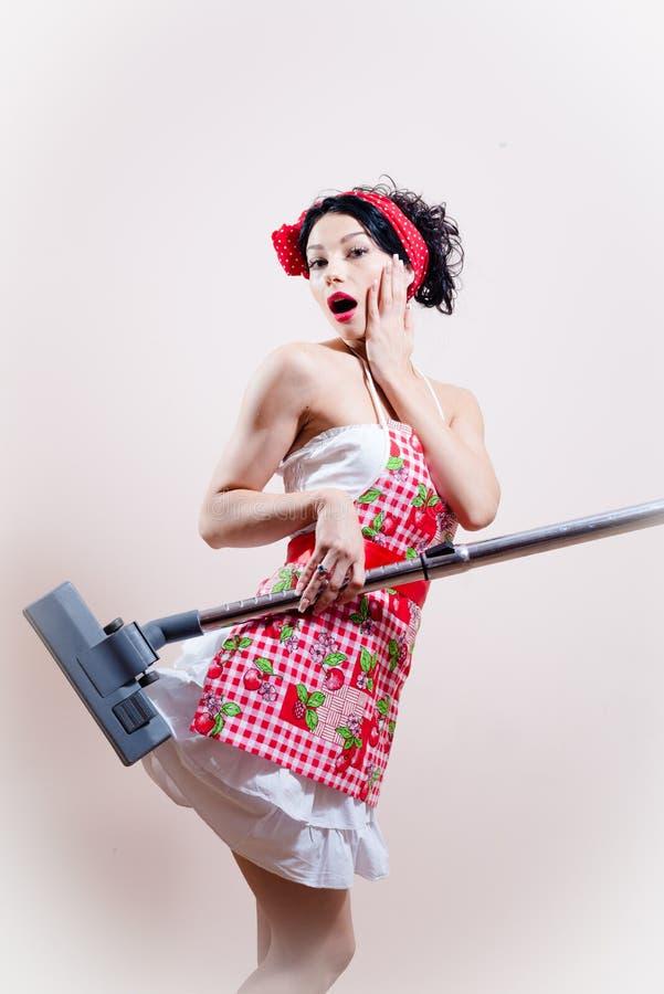 Hongerige stofzuiger: mooie grappige huisvrouwen sexy jonge vrouw die schort dragen & verraste camera bekijken royalty-vrije stock afbeeldingen