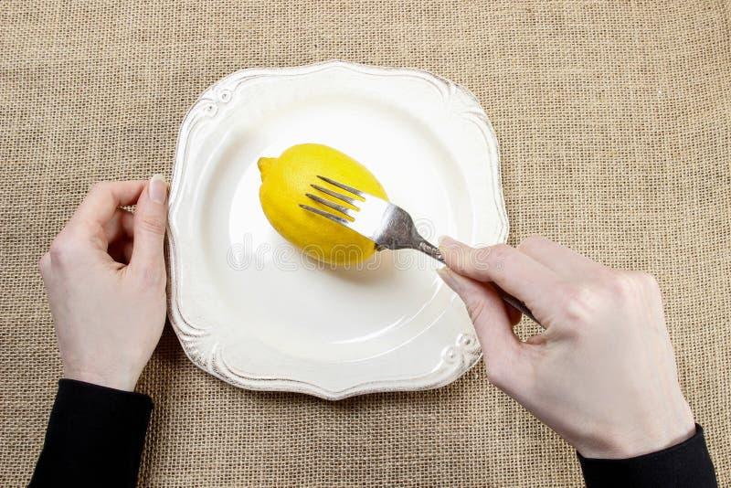 Hongerige vrouw die citroen eten stock foto