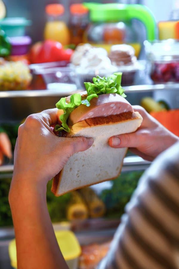 Hongerige Vrouw die een sandwich in zijn handen houden en volgende t bevinden zich royalty-vrije stock afbeelding