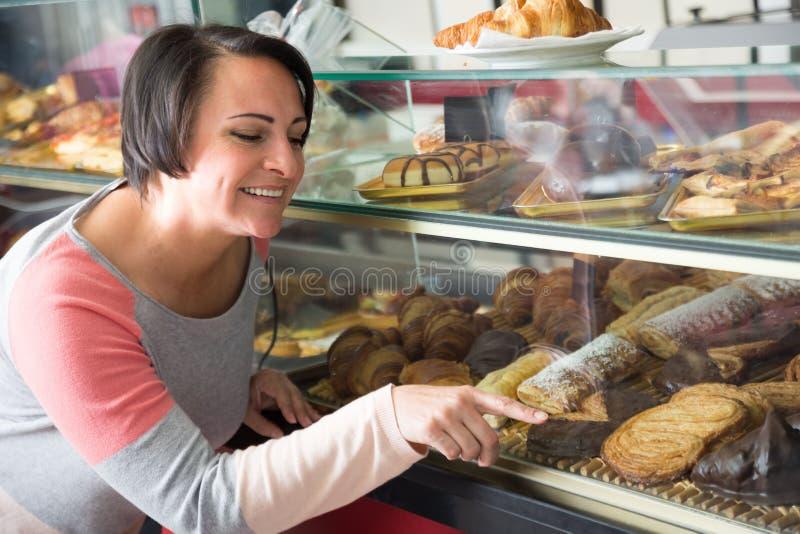 Hongerige vrouw die het gebakje onderzoeken royalty-vrije stock foto