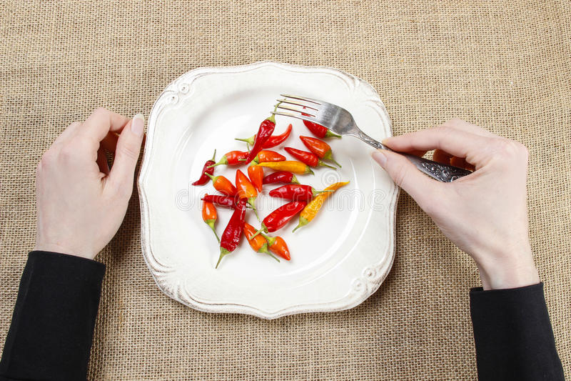 Hongerige vrouw die roodgloeiende Spaanse peperpeper eten Symbool van het aanpassen aan stock foto