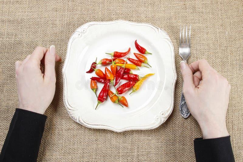 Hongerige vrouw die roodgloeiende Spaanse peperpeper eten Symbool van het aanpassen aan stock afbeelding