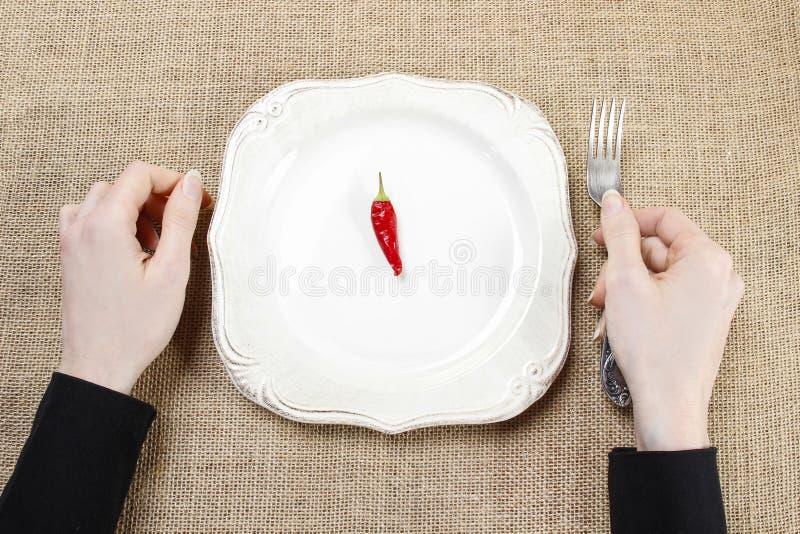 Hongerige vrouw die roodgloeiende Spaanse peperpeper eten Symbool van het aanpassen aan royalty-vrije stock foto