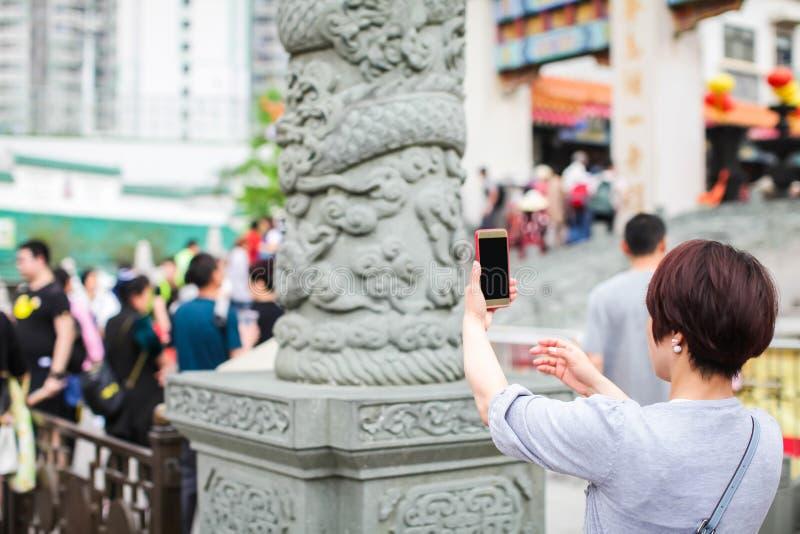 HONGKONG, China - APRIL 2018: occasionele vrouwelijke bezoeker van wongtai zondetempel in Hong Kong die beeld van steendraak neme royalty-vrije stock afbeeldingen