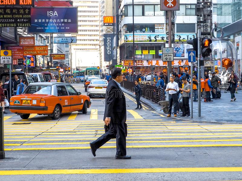 HONGKONG, CHINA - December 9 2016: Business man walking across the crosswalk on the road with city background. Hong Kong royalty free stock photos