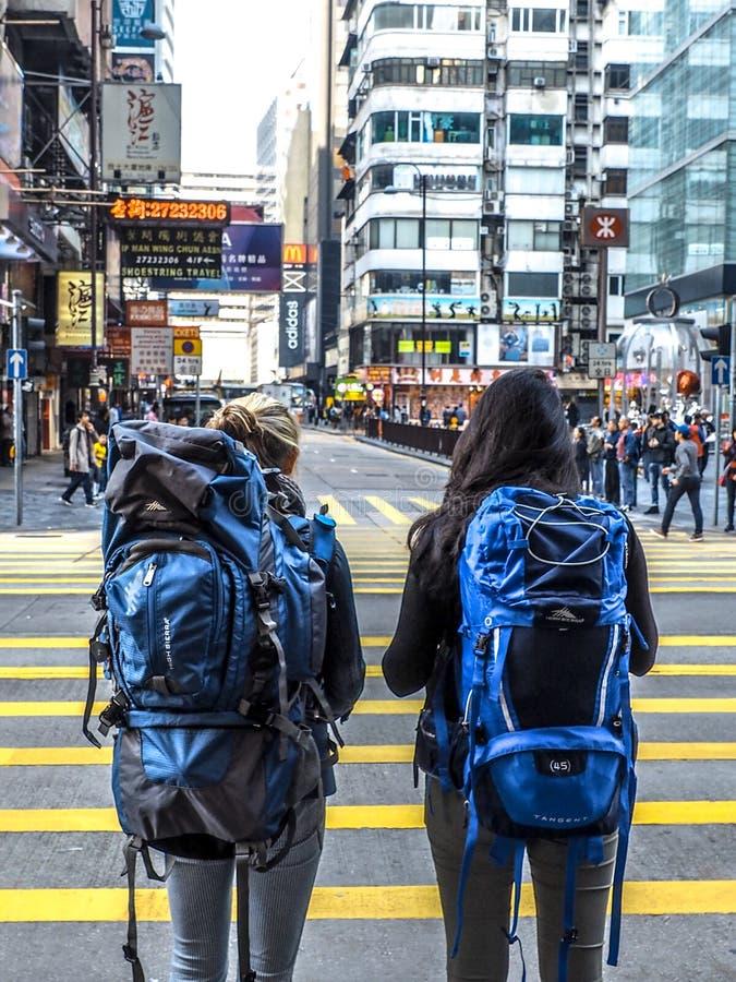 HONGKONG, CHINA - December 9 2016: Jong Meisje twee met rugzak over het zebrapad op de weg met stadsachtergrond Hon Kong stock foto's