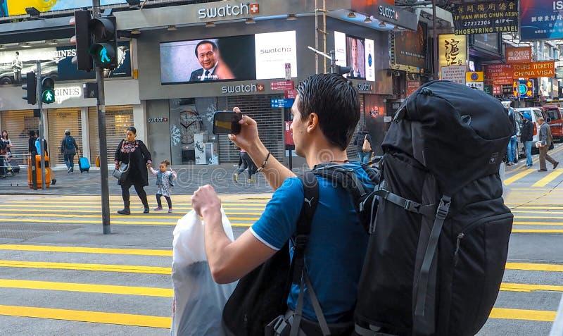 HONGKONG CHINY, Grudzień, - 9 2016: Młody człowiek z bagaż torbą na miasto ulicie z mapą w Hong Kong, bierze fotografię z mądrze  obraz royalty free