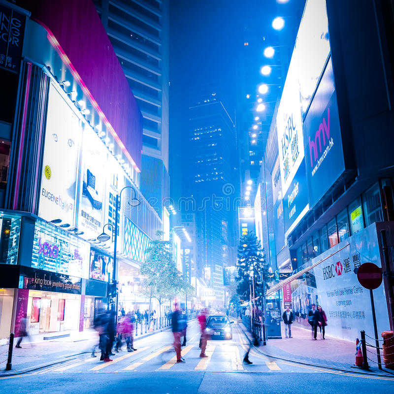 Honh Kong night street with illuminated shopping malls and walking people stock images