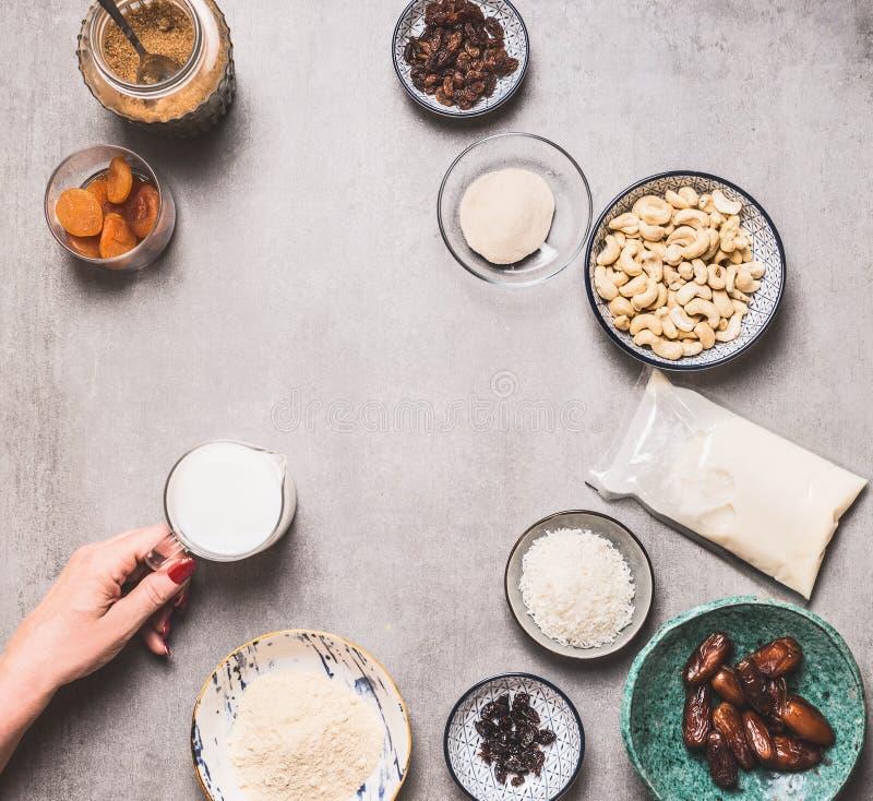 Honhand som har föga jug med icke-mjölk på betong med ingredienser i vegan glutenfria kakor: cashew, mandel arkivbild