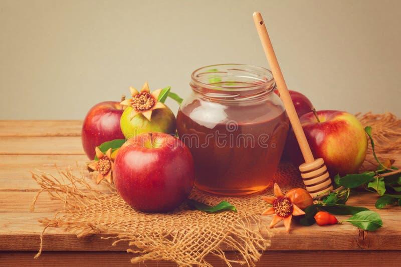 Honig, Apfel und Granatapfel auf Holztisch Retro- Filtereffekt lizenzfreies stockfoto