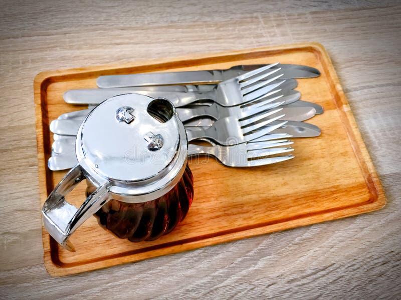 Honig für die Spitze des Nachtischs im kleinen Krug mit Gabeln und Messern auf hölzernem Behälter lizenzfreie stockfotos