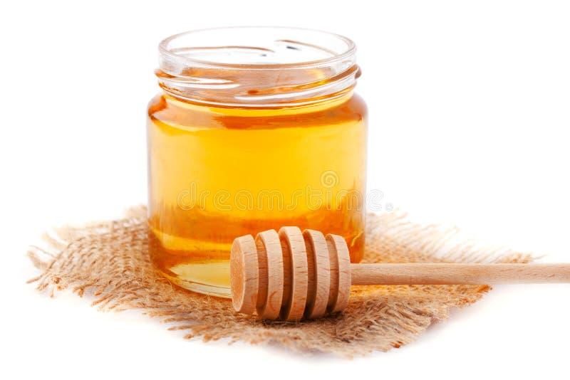 Honig im Glas mit einem hölzernen Löffel lokalisiert auf Weiß stockfotografie