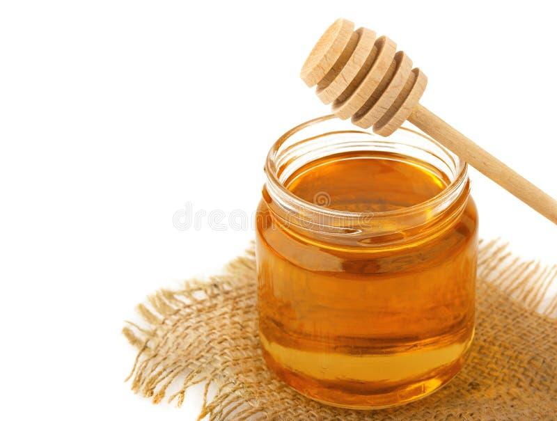 Honig im Glas mit einem hölzernen Löffel lokalisiert auf weißem Hintergrund lizenzfreie stockbilder