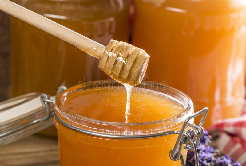 Honig und Glas mit Honig stockbild