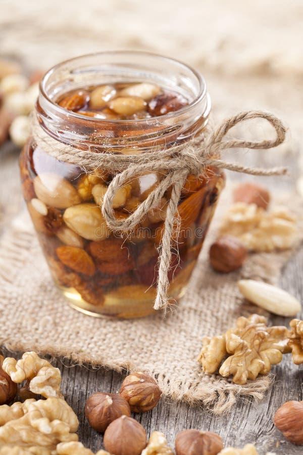 Honig und Mischnüsse lizenzfreie stockfotografie