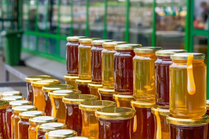 Honiggläser auf dem Markt stockbilder