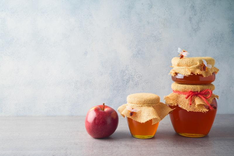 Honiggläser und -apfel über grauem Hintergrund lizenzfreie stockbilder