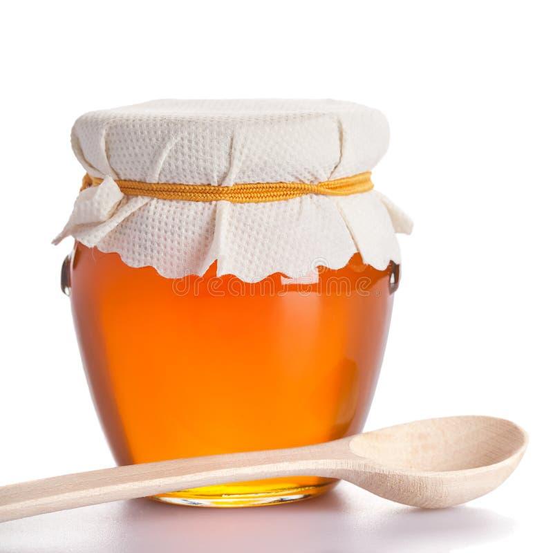 Honigglas mit dem hölzernen Löffel lokalisiert stockfotos