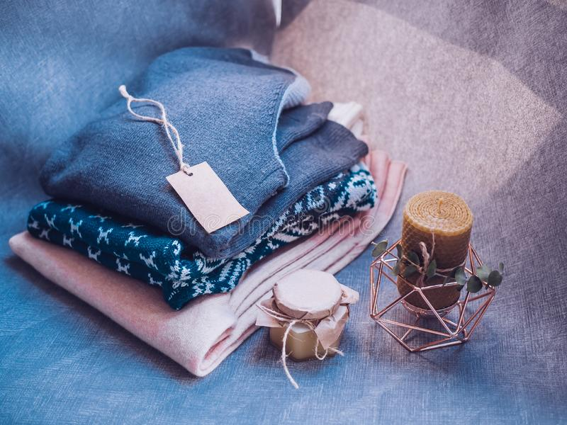 Honigkerze und warme woolen Strickjacke, verziert mit geführten Lichtern, Spitzenstandpunkt stockbild
