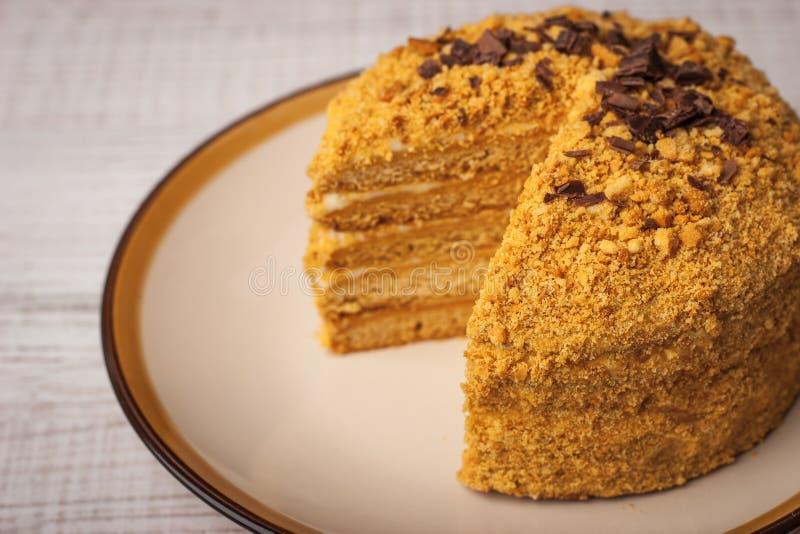 Honigkuchen mit Schokoladensplittern und Scheibe herausgeschnitten lizenzfreie stockfotos