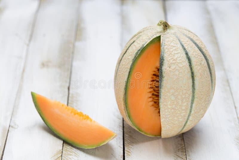 Honigmelonenschnitt offen auf weißem hölzernem Hintergrund lizenzfreie stockbilder