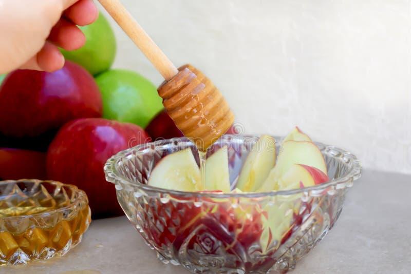 Honigschöpflöffel, Honig und helle klare farbige Äpfel stockfoto