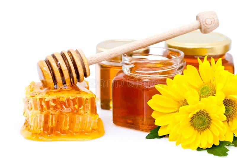 Honigschöpflöffel und -bienenwabe lizenzfreie stockbilder