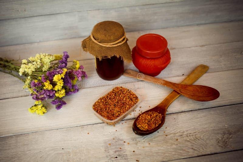 Honing, bijenstuifmeel en bloemen op een houten achtergrond stock afbeeldingen