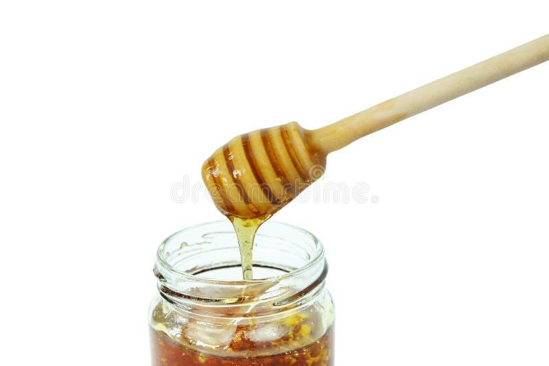 Honing die in glaskruik en houten die dipper druipen op een witte achtergrond, concept wordt geïsoleerd bijenproducten royalty-vrije stock foto