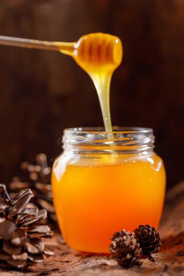 Honing die van het eetstokje in een glaskruik tegen de achtergrond van boomschors en kegels stromen royalty-vrije stock fotografie