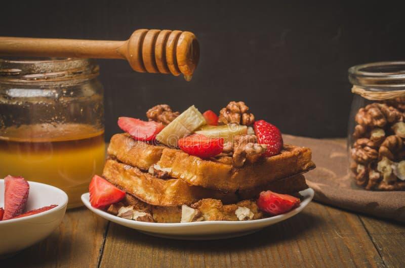 Honing die van honingsdipper op verfraaide wafeltjes, met aardbei, banaan en okkernoot druipen Selectieve nadruk royalty-vrije stock foto