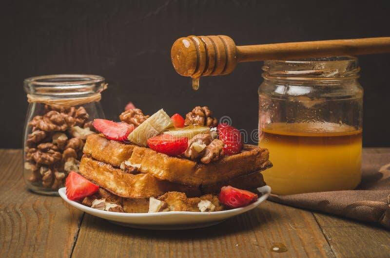 Honing die van honingsdipper op verfraaide wafeltjes, met aardbei, banaan en okkernoot druipen Selectieve nadruk stock foto's