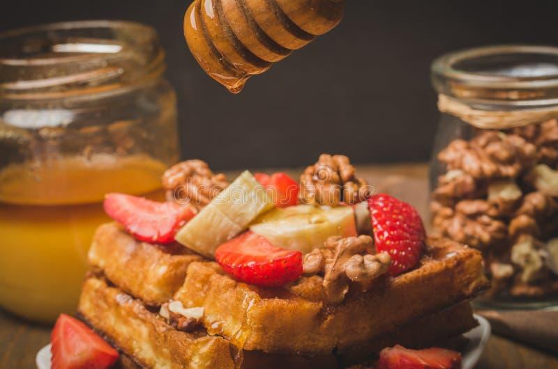 Honing die van honingsdipper op verfraaide wafeltjes, met aardbei, banaan en okkernoot druipen Sluit omhoog royalty-vrije stock foto's