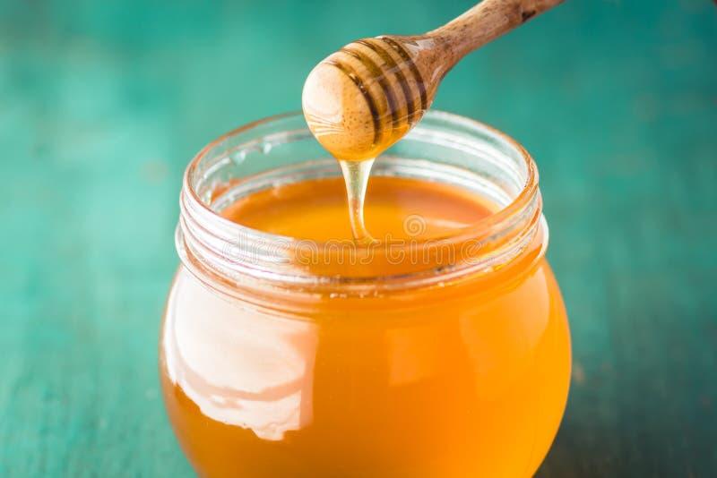Honing in een glasfles op blauw hout in laag licht stock fotografie