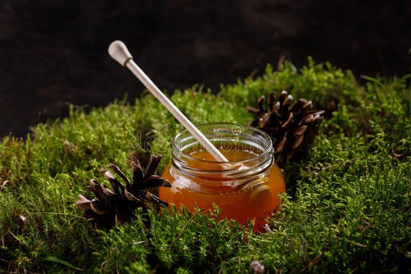 Honing in een glaskruik met een houten honingsstok op houten mos stock foto's