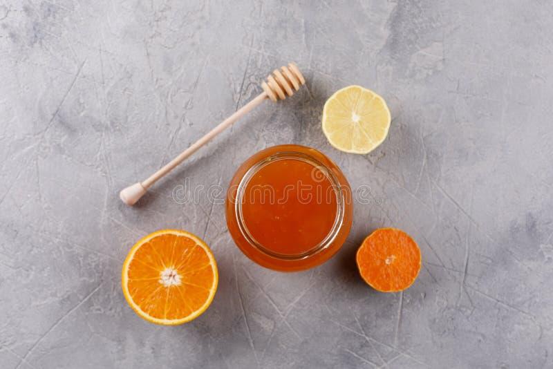 Honing in een glaskruik Reeks tegen koude met citrusvruchtensinaasappel en citroen stock foto