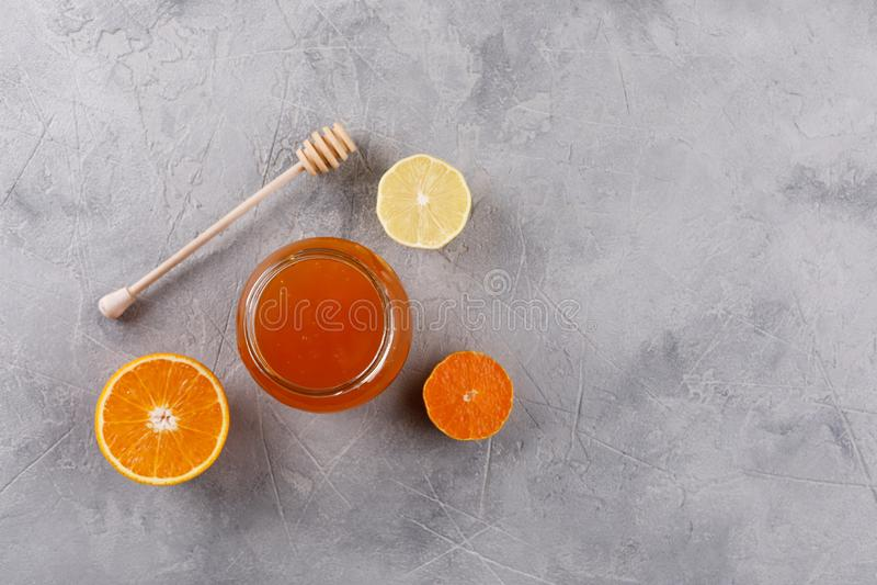 Honing in een van de glaskruik en honing stok Reeks tegen koude met citrusvruchtensinaasappel en citroen stock afbeeldingen