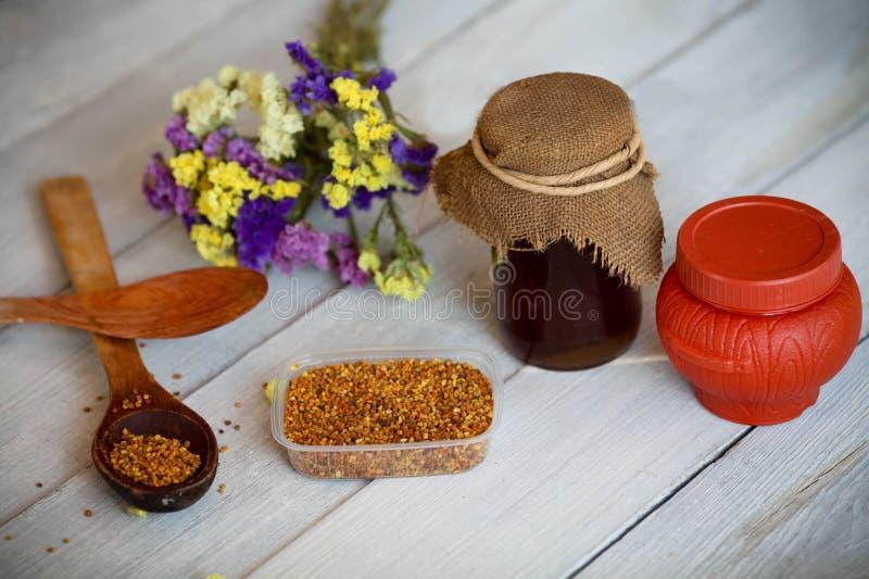 Honing en bijenstuifmeel op een houten achtergrond royalty-vrije stock fotografie