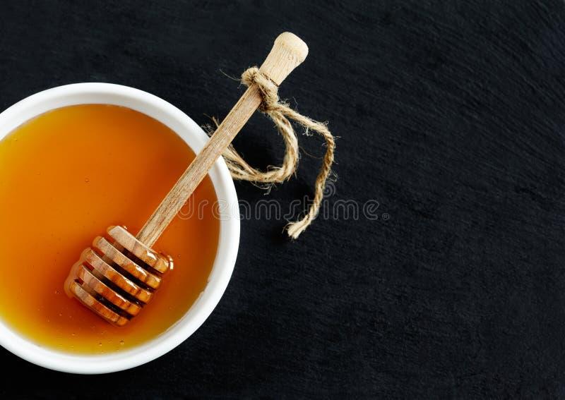 Honing en honingsdipper op zwarte achtergrond stock foto's
