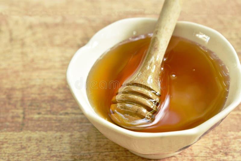 Honing en houten lepel in kop op lijst stock fotografie