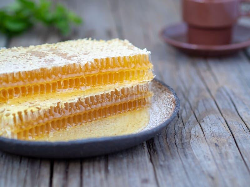 honing in honingraat op plaat op een oude houten lijst, close-up, zijaanzicht royalty-vrije stock afbeelding