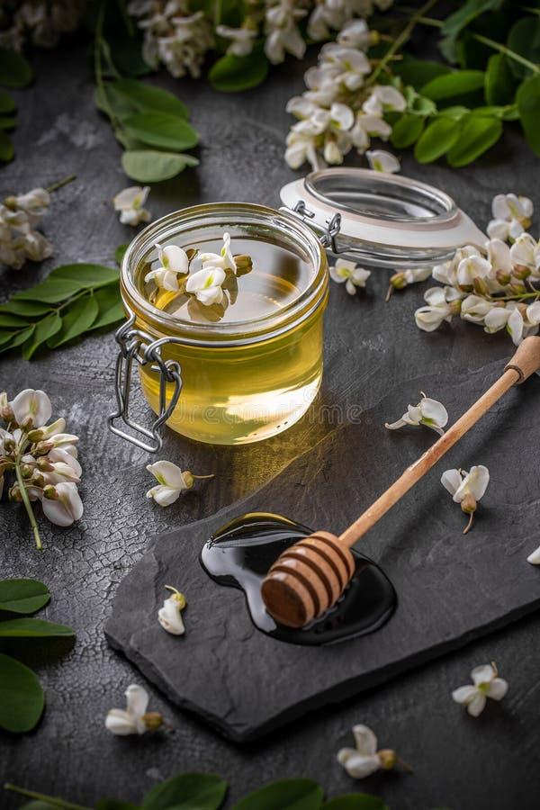 Honing in kruik met honingsdipper stock afbeelding