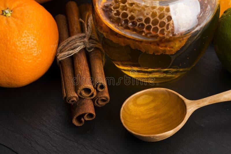 Honing met citrusvruchten en kaneel stock afbeeldingen
