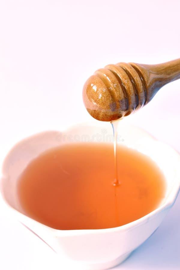 Honing op houten lepeldaling aan kop op witte achtergrond royalty-vrije stock afbeeldingen
